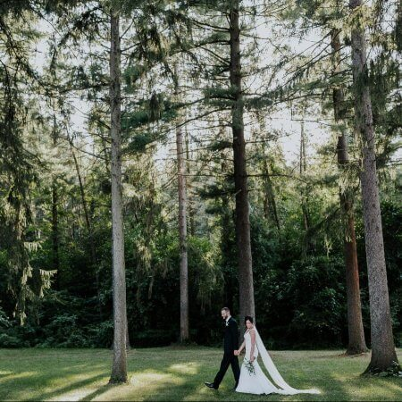 Bride and groom walk in the woods at Morris Estate