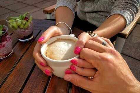 Two sets of hands hold one coffee cup