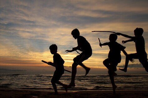 Kids with sticks at beach silhouetted against Michigan sunset
