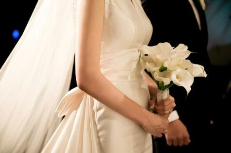 Bride holds bouquet standing next to groom