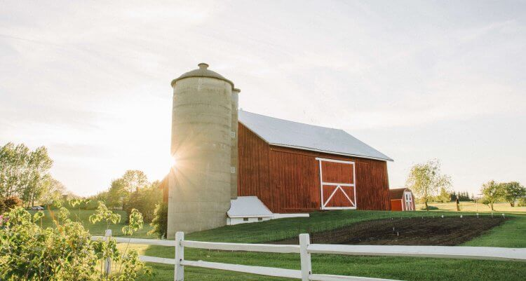 Sun sets behind red barn and its silo