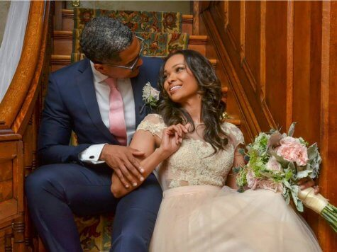Man and women sit on the stairs after vows renewal at Historic Webster House