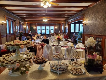 Beautiful dessert spread in the foreground as guests enjoy a tea party at Saravilla.