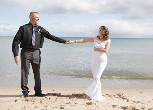 A bride and groom hold hands at the beach at Huron House