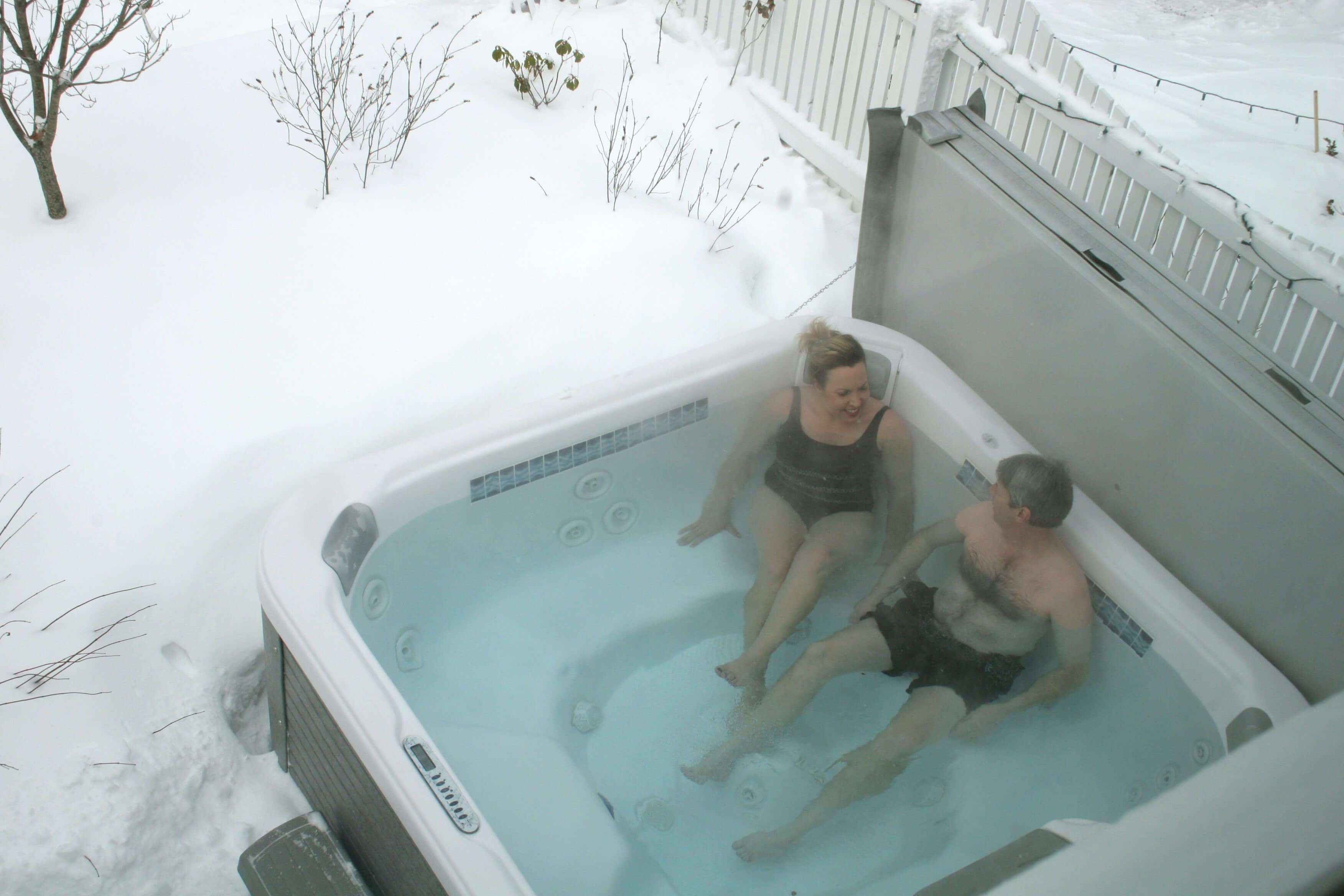 Couple sits in outdoor hot tub on a snowy day