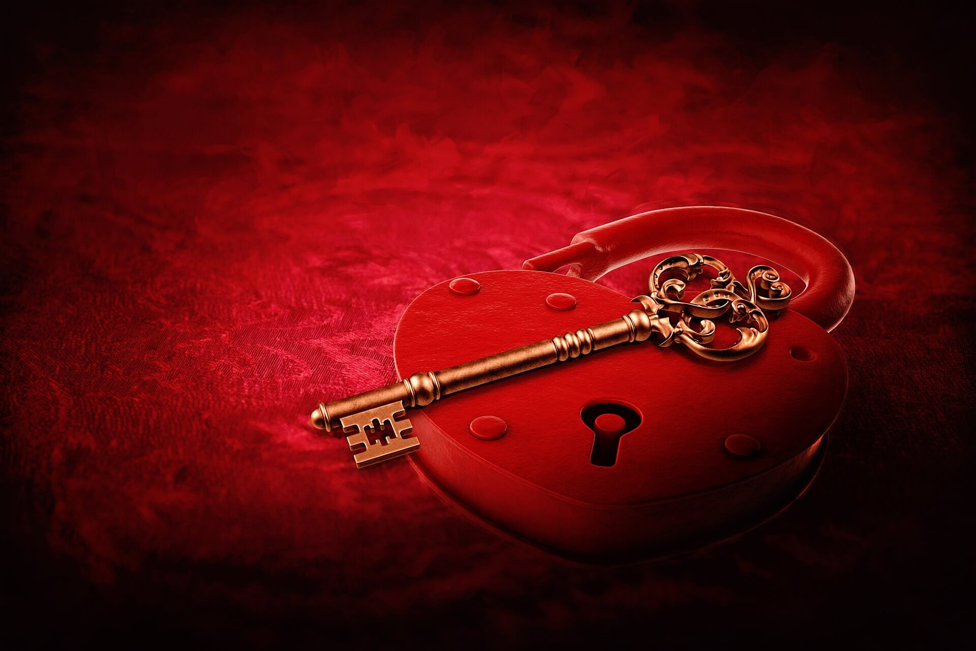 A red heart and a brass key on a red background