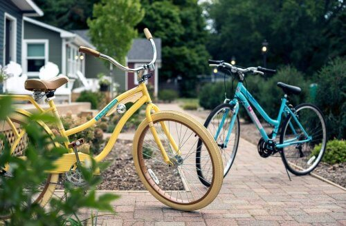 Two Hotel Saugatuck bikes are parked on the sidewalk outside the bungalows