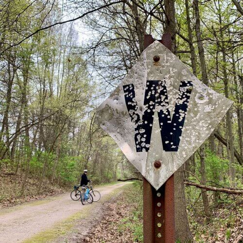 "A diagonal sign alongside the Polly Ann Trail says only ""W"" and has numerous bullet holes"