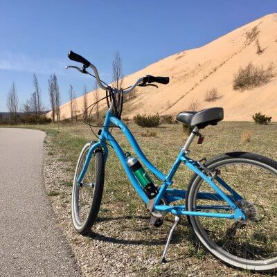 Blue bike stands along paved trail with Sleeping Bear Dunes in background.