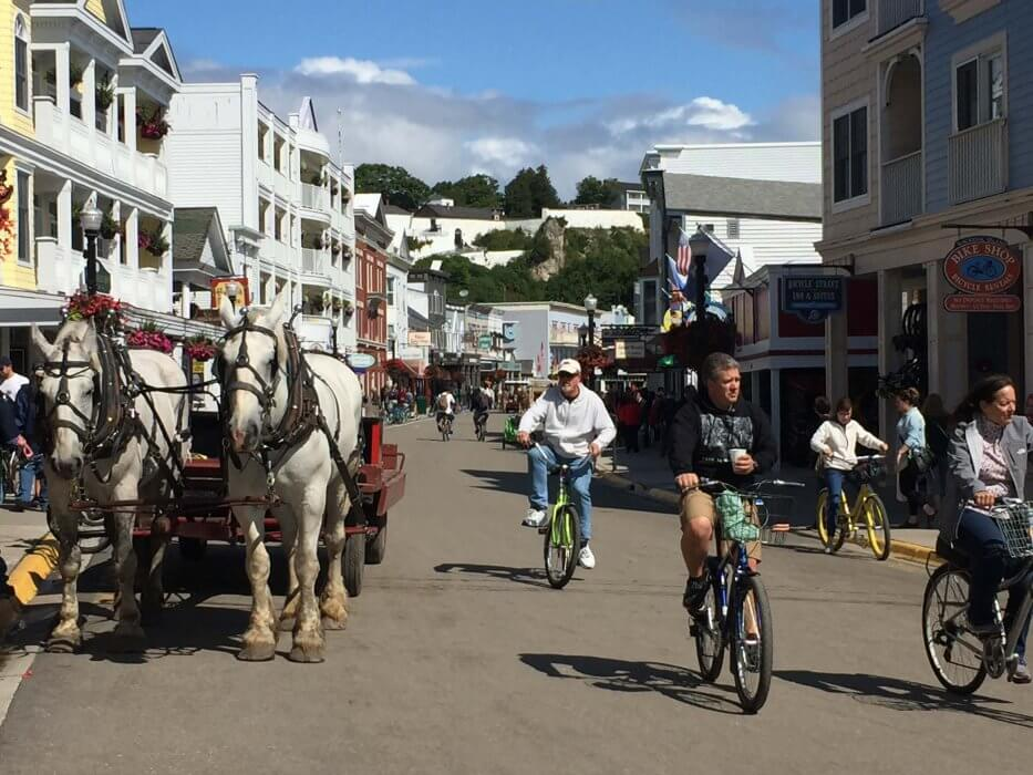 Horse-drawn wagon and bicycles share the Michigan bike trail on Mackinac Island