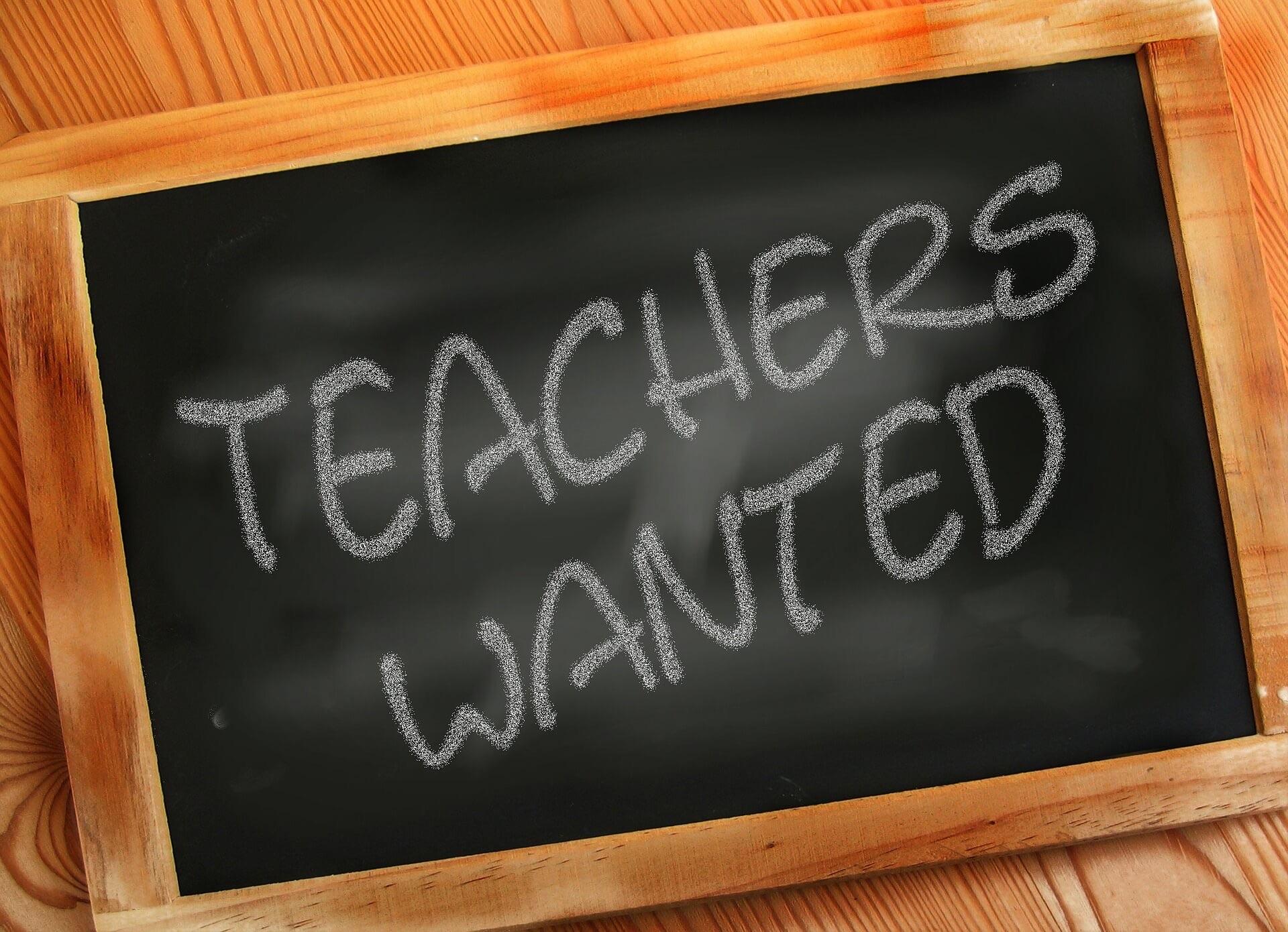 "Photo illustration: A framed blackboard with ""Teachers Wanted"" written in chalk"