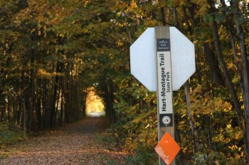 A sign for the Hart-Montague Trail stands alongside trail covered with fall leaves.