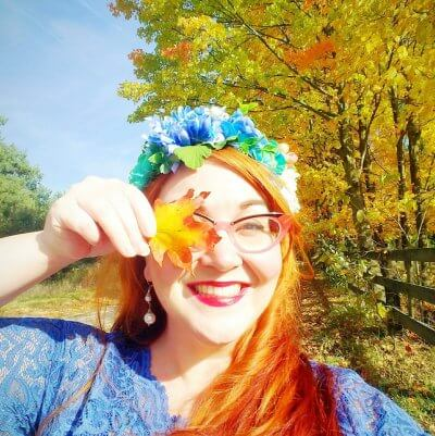 Briana playfully holds an autumn leaf over one eye.