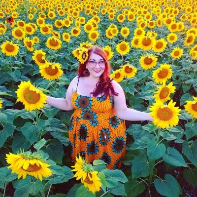 Model and fashion blogger Briana Herzog poses in a vintage-style floral dress in a field of sunflowers.