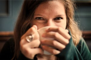 Woman's hands wrap around a mug of coffee or tea
