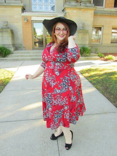 Briana Herzog in vintage print dress, hat and glasses.