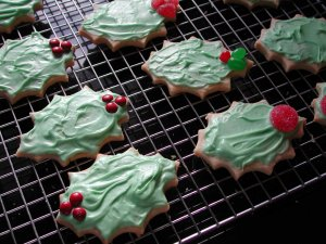 Fresh baked holiday cookies in the shape of holly leaves, with green icing and candy berries.