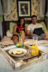 Breakfast in Bed with couple in the background