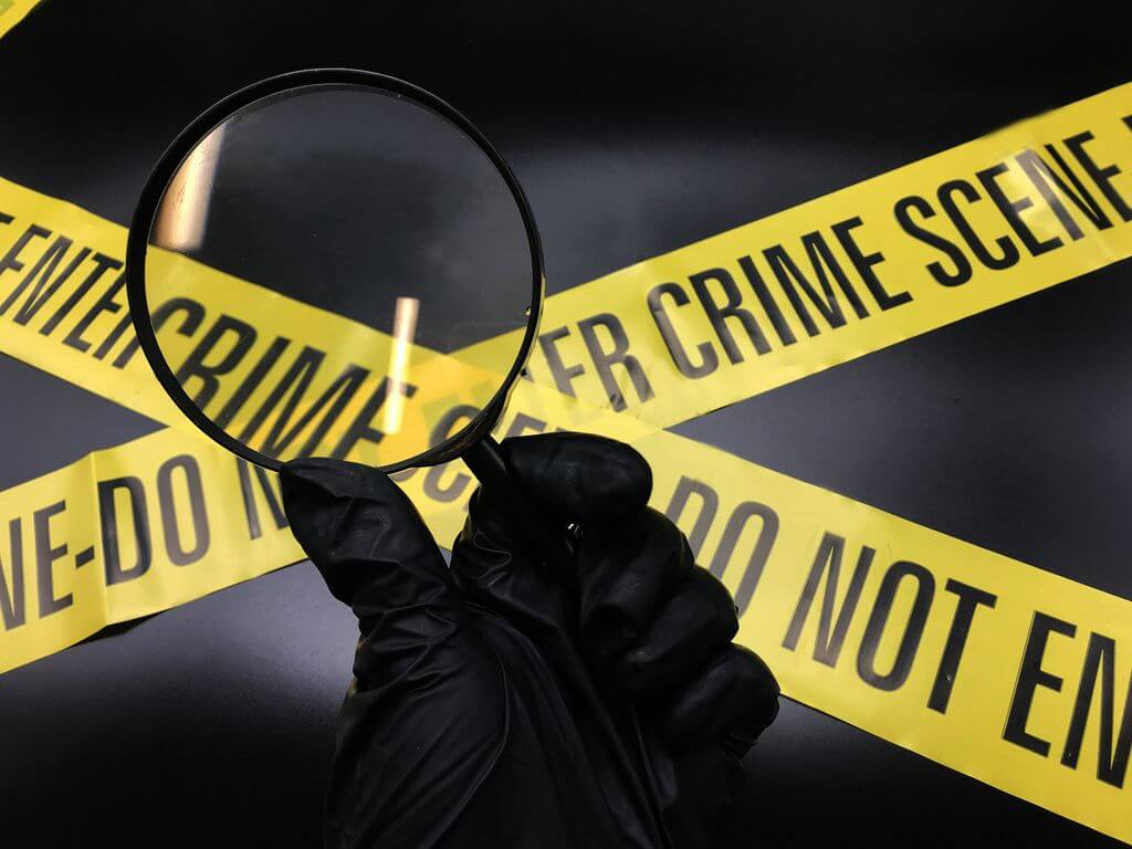 Crime tape with a hand and magnifying glass