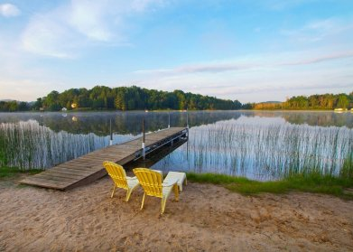Two Adirondack chairs face beautiful view of sky and lake.