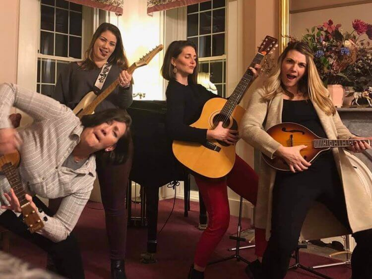 Four women pretend to play guitars and other musical instruments in the music room at Munro House