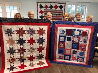 Quilters at Hankerd Inn hold up patriotic quilts they made