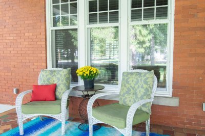 White wicker chairs with green cushions on porch at Nordic Pineapple