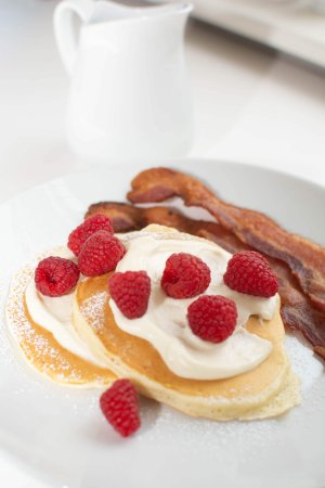 Pancakes with raspberries and bacon served at Nordic Pineapple