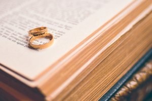 Photo illustration showing two gold bands on an open book