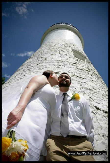 Wedding couple poses for photo in front of Old Presque Isle Lighthouse.