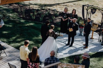 A bridal couple approaches the officiant at Oak Creek Lodge.