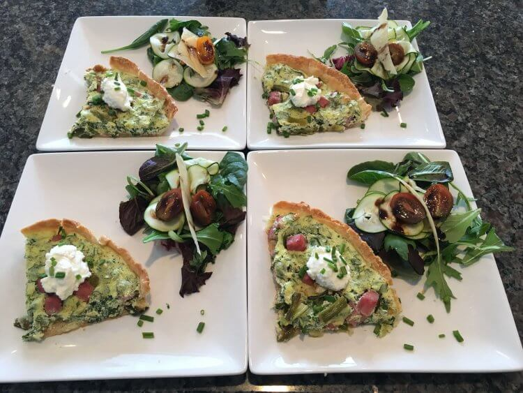 Four beautifully arranged plates of ham and asparagus quiche with an arugula and spinach salad.