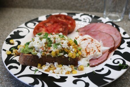 Avocado toast as served at Hart House with sliced ham, sliced tomatoes and a poached egg