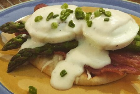 Two oven-'poached' eggs nestled on top of a toasted multi-grain flatbread with melted Havarti cheese, oven-crisped bacon, asparagus spears, topped off with a béchamel sauce, and a few scallions for garnish.