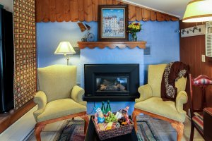 Cozy wing chairs in front of fireplace in Lane's Cottage at the Glen Arbor Bed & Breakfast in Glen Arbor, Michigan.e