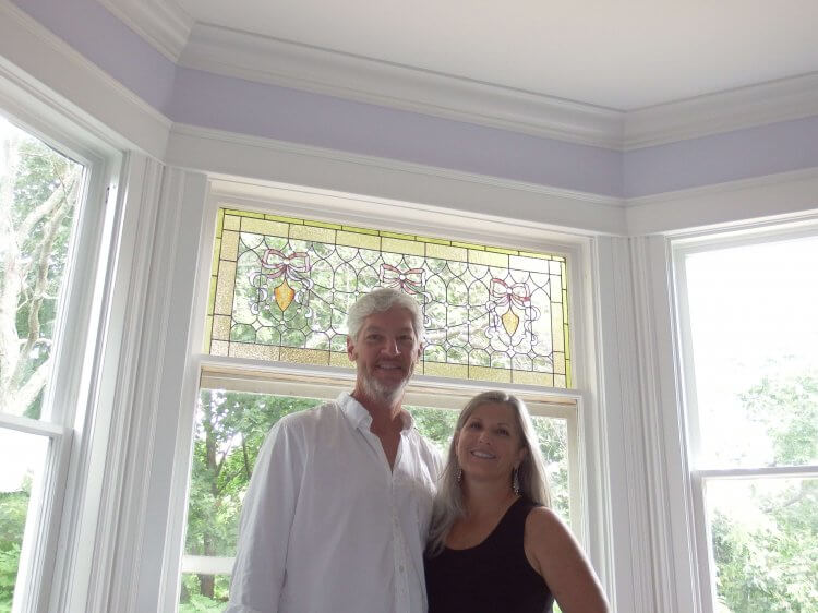 Aspiring innkeepers Lance and Joanne Murphy stand in front of one of the many stained glass panels that were refurbished and reinstalled in the future Port Austin B&B