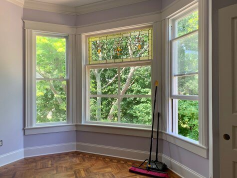Bay window in a guest room overlooks trees in the side yard and shows renovated