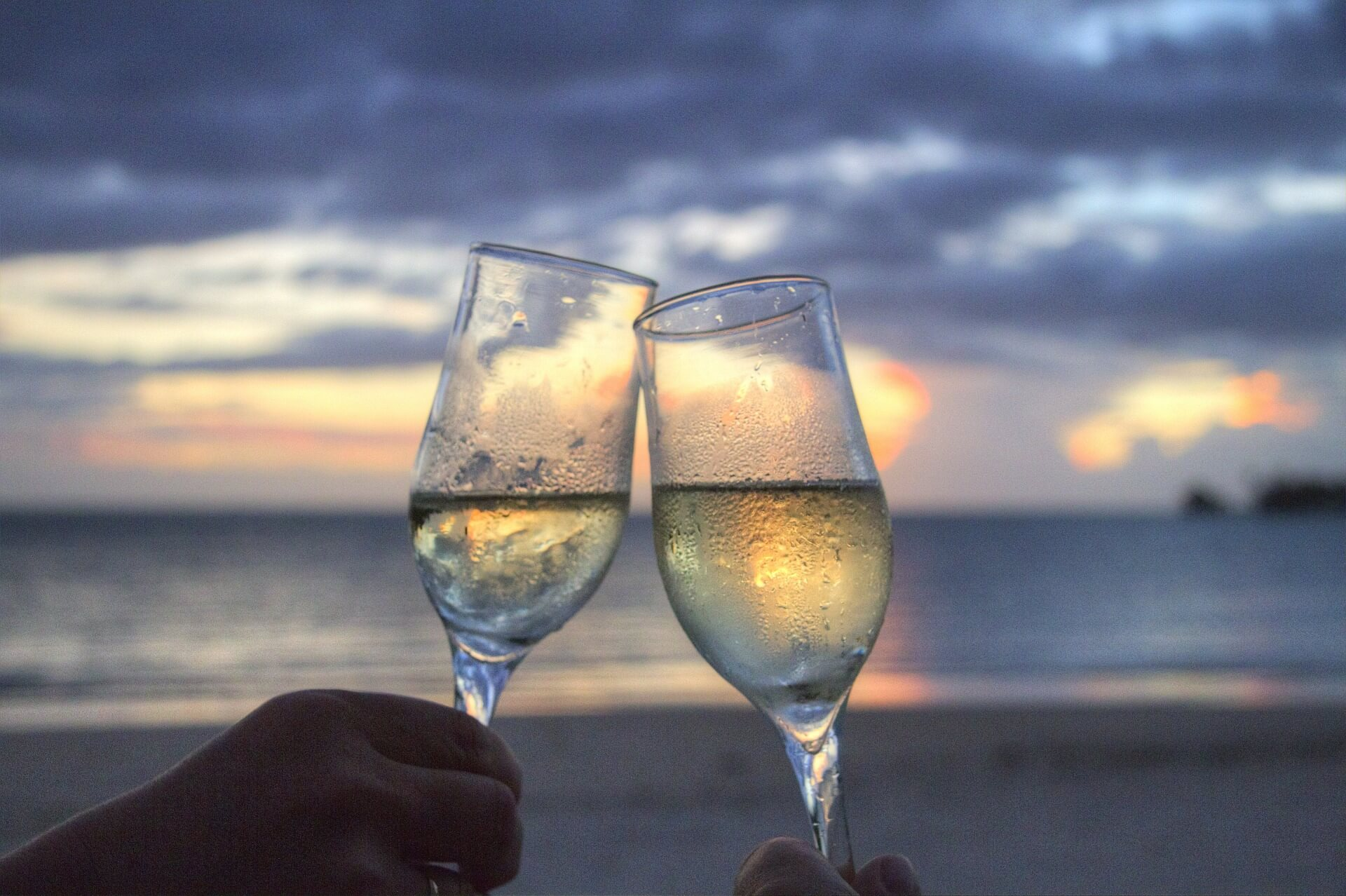 Unseen hands toast two glasses of white wine in front of a lake scene at sunset
