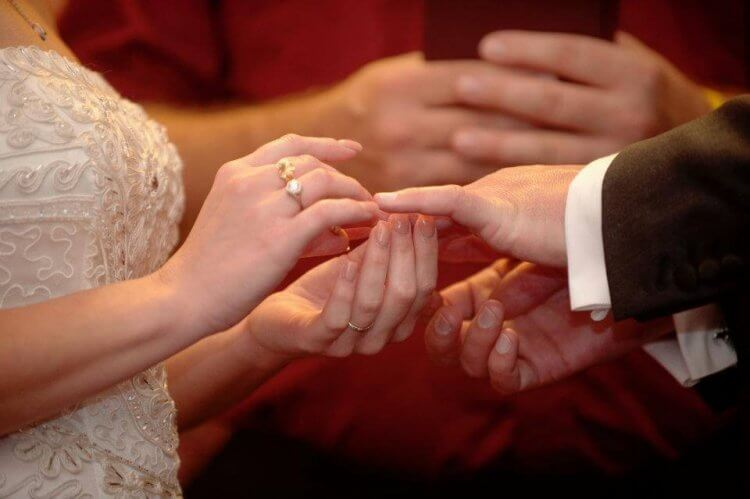 Closeup photo of bride placing a ring on the groom's finger.