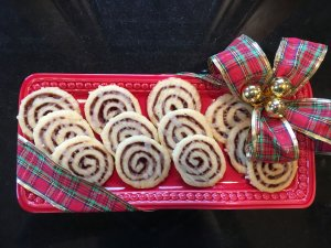 Cinnamon Bun Cookies on Red Square Plate tied with a plaid holiday bow.