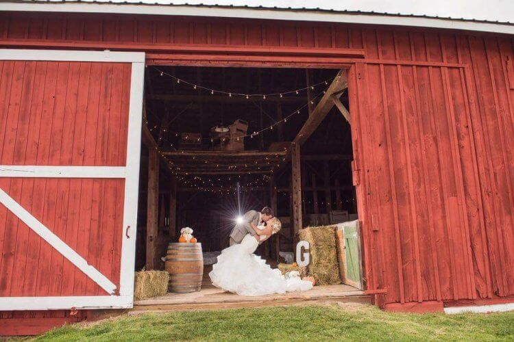 Bride and groom embrace inside the door of the red barn at the Farmhouse B&B