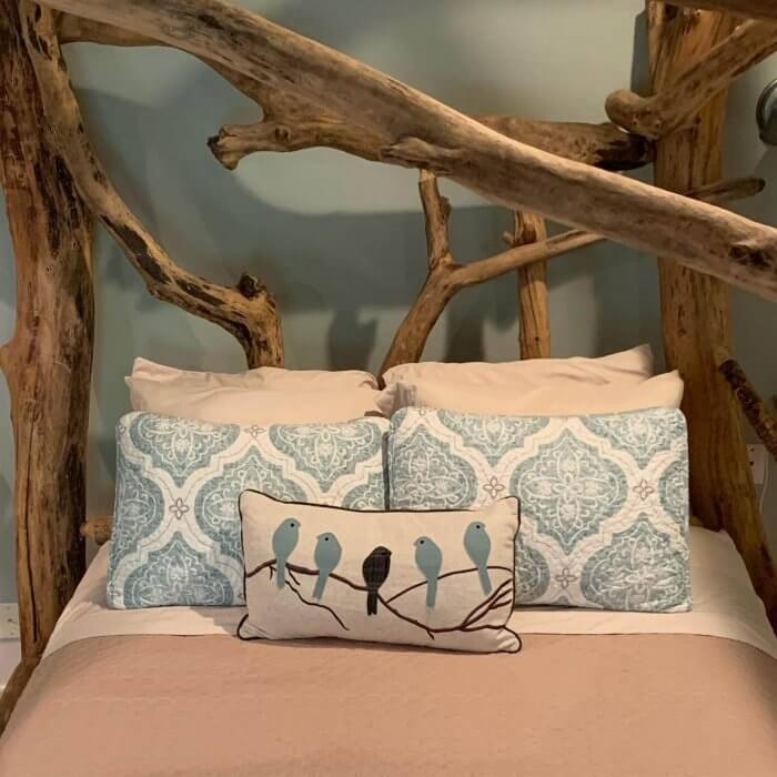 Tree branches form the headboard of a bed at Goldberry Woods, high on our list of Michigan B&Bs you need to try..