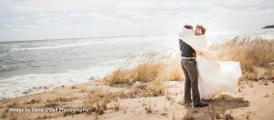 A newlywed couple embraces on cold, windy beach at Huron House