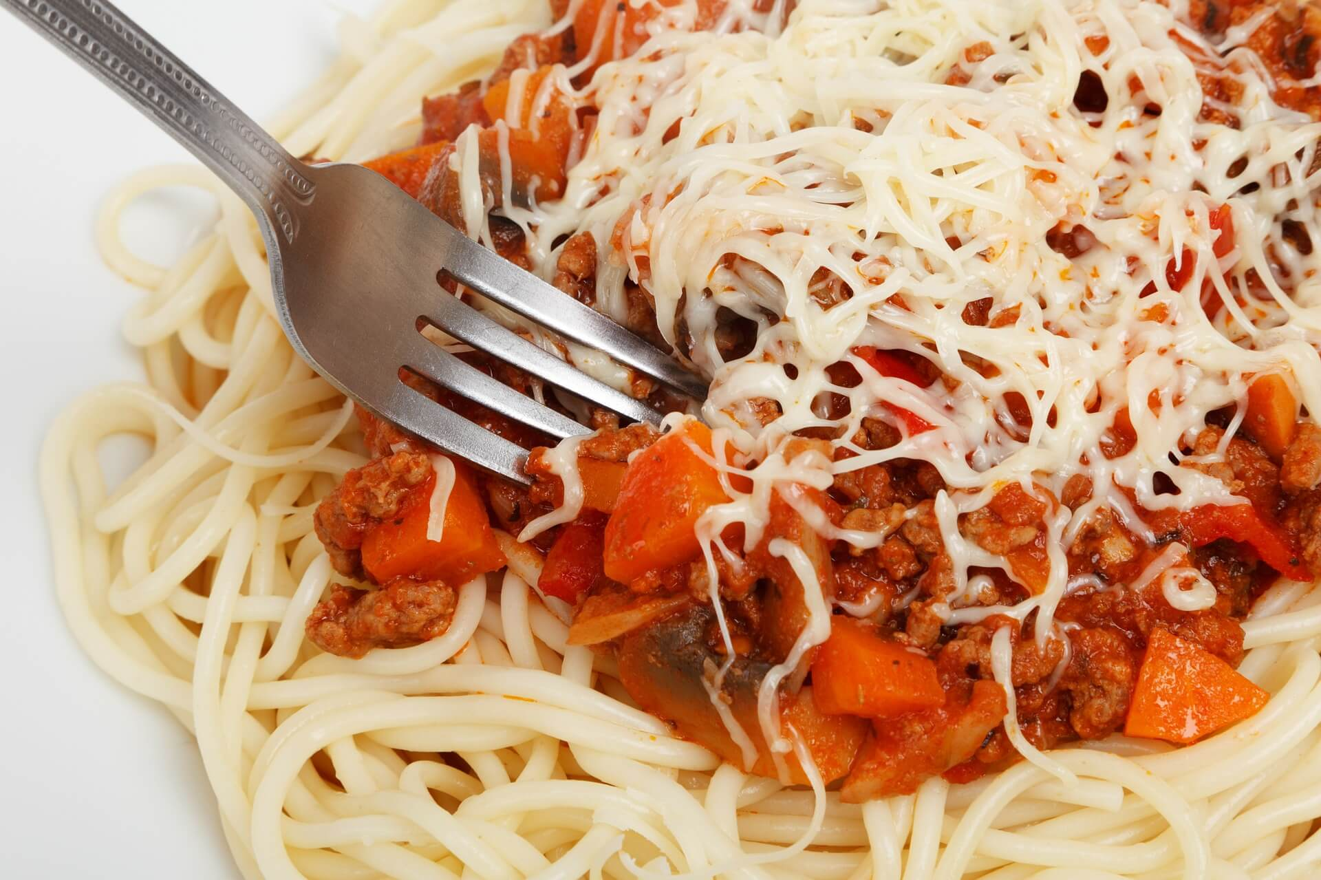 Fork tines in a plate pf pasta with marinara sauce