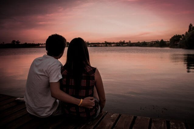 Man embraces woman as they gaze at lake at dusk
