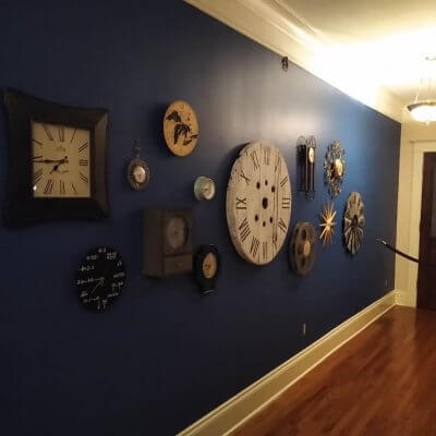 Dark blue walls accent a collection of clocks