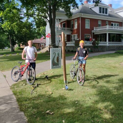 A man and woman stand with their bikes in front of The Nordic Pineapple B&B.