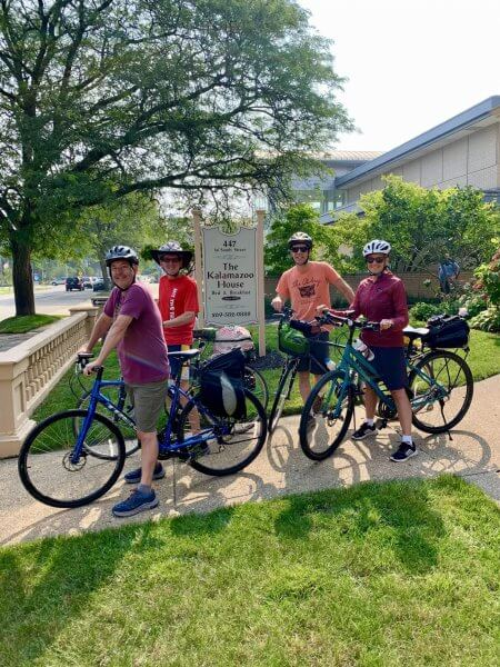 Four bicyclists stand in front of Kalamazoo House