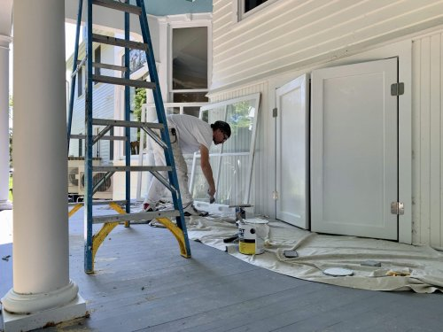 Painter works on trim at Port Austin Bed and Breakfast