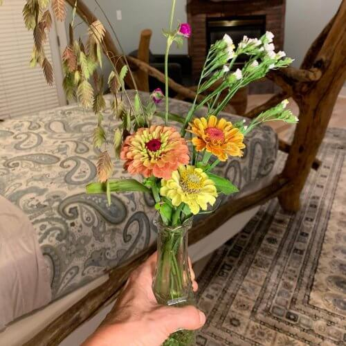 Innkeeper's hand holds a vase of early fall flowers from the inn's garden.